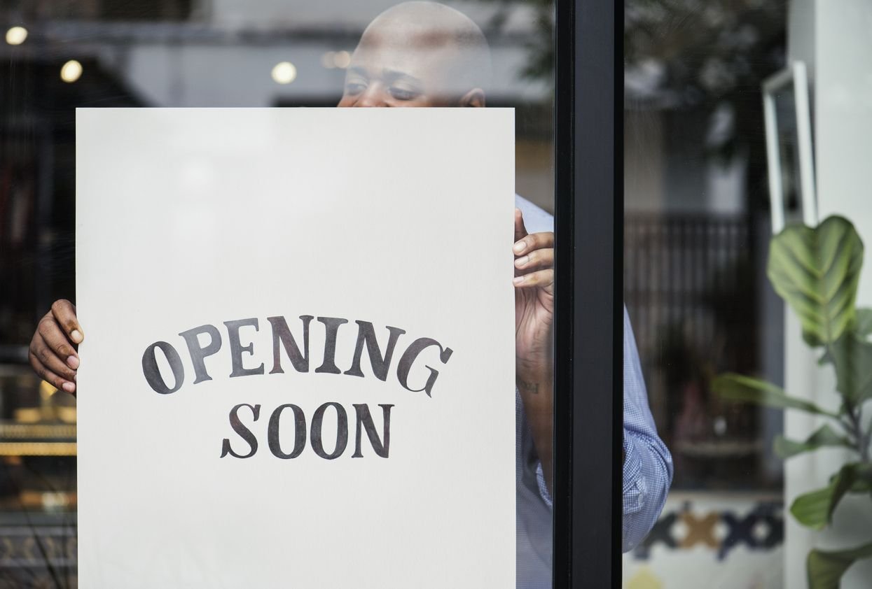 PointofSale.com Owner hanging opening soon sign Startup Money for Small Business